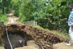 Espos/Bony Eko Wicaksono Kepala Desa Pare, Kecamatan Selogiri, Sugeng menunjukkan kondisi jembatan di Desa Pare yang ambrol, Minggu (8/2/2015). Akses penghubung antara Desa Pare dengan Desa Keloran, Kecamatan Selogiri putus pascaambrolnya jembatan. (Bony Eko Wicaksono/JIBI/Solopos)