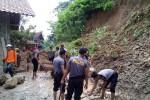 Petugas dari Kepolisian Resort Kulonprogo dan warga gotong royong membersihkan material longsor di salah satu rumah warga di Dusun Sarimulyo, Desa Gerbosari, Samigaluh, Selasa (10/2/2015). (JIBI/Harian Jogja/Holy Kartika N.S.)