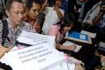Aktivis Indonesia Corruption Watch (ICW), Firdaus Ilyas (kiri), Febri Hendri (kedua dari kiri), dan Siti Juliantari (tengah) membawa berkas terkait dugaan korupsi APBD DKI Jakarta Tahun 2014 di Gedung Komisi Pemberantasan Korupsi (KPK), Jakarta, Kamis (26/3/2015). ICW melaporkan indikasi dugaan korupsi pengadaan barang dalam APBD DKI 2014 dan mendesak KPK memperluas kasus itu terutama untuk mata anggaran yang diajukan DPRD. (JIBI/Solopos/Antara/Fanny Octavianus)