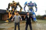 Yu Lingyu (kiri) dan Yu Zhilin (kanan) berpose di depan replika Transformers. (Dailymail.com)