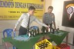 Kapolsek Kebakkramat, AKP Lukman Tri Novianto (kiri), menunjukkan minuman keras (miras) yang dirazia dari penjual keliling di Kebakkramat, Senin (16/3/2015). (Bayu Jatmiko Adi/JIBI/Solopos)