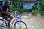 Warga melintasi banjir di Tawangrejo, Kota Madiun, Jawa Timur, Rabu (25/3/2015). Akibat hujan deras sepanjang Selasa (24/3/2015) malam, sejumlah wilayah di kota dan Kabupaten Madiun terendam banjir, menyebabkan arus lalu lintas lumpuh di sejumlah lokasi, ratusan rumah terendam dan tiga sekolah dasar diliburkan. (JIBI/Solopos/Antara/Siswowidodo)