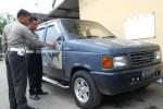 Petugas Satlantas Polres Sragen memeriksa mobil Isuzu Panther berpelat nomor AD 9489 NF yang terlibat kecelakaan lalu lintas di Jalan Raya Sragen-Solo, Minggu (1/3/2015) lalu. (Kurniawan/JIBI/Solopos)