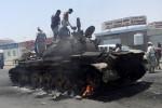 Warga berdiri di atap tank yang terbakar saat terjadi pertempuran di jalan di kota selatan Yaman, Aden, Minggu (29/3/2015). (JIBI/Solopos/Reuters)