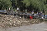 Warga bersama anggota TNI, polisi, dan linmas bergotong royong membersihkan sampah yang tersangkut di Jembatan Biru di Kampung Mipitan, Jebres, Solo, Kamis (23/4/2015). Pagar pembatas jembatan patah setelah diterjang derasnya arus air Kali Anyar. (Ivanovic Aldino/JIBI/Solopos)