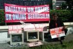 Aktivis asal Kota Solo, Bambang Saptono, Kamis (9/4/2015), memprotes rencana pelaksanaan ujian nasional (UN) berbasis komputer dengan memasang spanduk di depan Kantor Dinas Pendidikan, Pemuda, dan Olahraga (Disdikpora) Kota Solo. (Septhia Ryanthie/JIBI/Solopos)