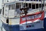 Dua nelayan memasang spanduk terima kasih kepada Presiden Jokowi di lambung kapal mereka yang tengah bersandar di Pelabuhan Paotere, Makassar, Sulawesi Selatan, Kamis (21/5/2015). (JIBI/Solopos/Antara/Darwin Fatir)