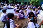 Sejumlah anak mengolah sampah dedaunan dan mengemas kompos yang sudah jadi ke dalam gelas plastik bekas air minum kemasan di halaman SDN Kalimenur, Rabu (27/5/2015). (JIBI/Harian Jogja/Holy Kartika N.S.)