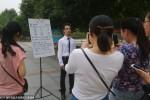 Ji berada di salah satu sudut kampus dengan papan persyaratan menjadi pacarnya (Shanghaiist.com)