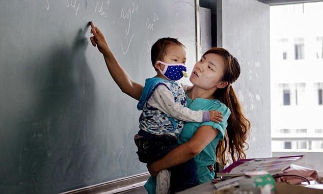Zhang Wei menggendong anaknya saat mengajar (Dailymail.co.uk)