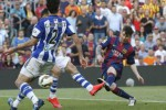 Barcelona's Lionel Messi kicks the ball against Real Sociedad's Mikel (L) and C. Martinez (C) during their Spanish first division soccer match at Nou Camp stadium in Barcelona