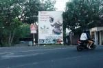 Seorang pengendara motor melintas di area ringroad utara, Kota Wonosari. Di pinggir jalan itu terdapat dua buah poster calon bupati yang akan maju dalam pilkada. foto diambil Selasa (19/5/2015). (JIBI/Harian Jogja/David Kurniawan)
