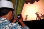 Penonton mengabadikan pergelaran wayang kulit semalam suntuk yang memainkan lakon Wahyu Nugraha Jati dengan dalang Ki Anom Suroto di Alun-Alun Jombang, Jawa Timur, Kamis (11/6/2015) malam, rangkaian kegiatan Kenduri Sukses Muktamar Ke-33 NU. (JIBI/Solopos/Antara/Syaiful Arif)