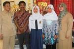 Mellina Abriyanti (tengah) berfoto dengan kedua orang tuanya dan Kepala Sekolah SMP Negeri 1 Wonosari Agus Suryana (kiri) di ruang kepala sekolah, Rabu (10/6/2015). (JIBI/Harian Jogja/David Kurniawan)