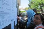 Petugas PPDB SMPN 4 Solo, Endang Teguh (kanan) memeriksa berkas siswa yang mendaftar PPDB online di SMPN 4 Solo, Senin (22/6/2015). (JIBI/Solopos/Eni Widiastuti)