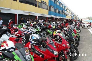 Ilustrasi helm diletakkan di atas tangki sepeda motor. (Tmcblog.com)
