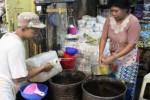 Pedagang menakar minyak curah di Pasar Legi, Rabu (1/7). Sejumlah harga kebutuhan pokok perlahan naik menjelang Lebaran. (Shoqib Angriawan/JIBI/Solopos)