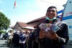 Seorang warga menunjukan satu paket penukaran uang baru usai mengantre panjang di loket penukaran uang mobil ATM yang diparkir di halaman Pemkab Kulonprogo, Senin (6/7/2015). (Harian Jogja/Holy Kartika N.S)