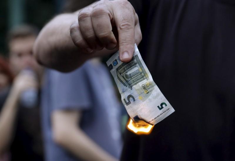 Demonstran anti pengetatan keuangan Yunani membakar selembar uang euro di luar Kantor Perwakilan Uni Eropa, Athena, Yunani, Minggu (18/6/2015). (JIBI/Solopos/Reuters/Alkis Konstantinidis)