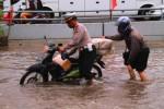 Polisi membantu pengendara saat banjir. (Istimewa/FB Polres Lamongan)