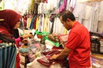 Pemilik As Shobu tengah melayani pembelian sajadah di kiosnya di Pasar Beringharjo, Jogja, Kamis (2/7/2015). (Harian Jogja/Kusnul Isti Qomah)