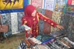 Penjaga salah satu stan batik, Sarwini, menunjukkan kain batik hasil kerajinan warga Desa Jarum, Bayat, Klaten, Minggu (23/8/2015), saat digelar festival dan pameran batik di desa setempat. (Taufiq Sidik Prakoso/JIBI/Solopos)