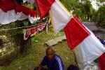 Penjual bendera asal Garut Jawa Barat, Ade Rahmat, berteduh di bawah bendera dagangannya, Jumat (31/7/2015). (Harian Jogja-Bernadheta Dian Saraswati)