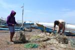 Beberapa nelayan di Pantai Congot, Temon, merapikan dan membersihkan jaring dari sampah-sampah yang tersangkut saat dipasang di tengah laut untuk menjaring ikan, Selasa (8/9/2015). (JIBI/Harian Jogja/Holy Kartika N.S.)