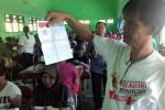 Kasubag Logistik KPU,Tantowi Nurdin, menunjukkan surat suara yang rusak saat berada di lokasi pelipatan surat suara, di aula SLB Wonogiri, Senin (16/11/2015). Terdapat noda tinta merah pada surat suara, tepat di belakang gambar pasangan calon.  (Bayu Jatmiko Adi/JIBI/Solopos)