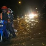 Pengendara mendorong sepeda motornya yang mogok menggunakan kaki saat melintas di Jl. Jenderal Sudirman yang tergenang banjir, Kamis (24/12/2015) malam. (Rudi Hartono/JIBI/Solopos)