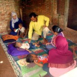 Ahli pengobatan tradisional, Darwi, mengobati tiga balita yang terbaring di lantai beralas tikar di Dukuh Geneng RT 001, Desa Cangkol, Kecamatan Plupuh, Sragen, Sabtu (30/1/2016). (Tri Rahayu/JIBI/Solopos)