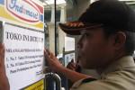 Petugas Satpol PP Sleman memasang segel penutupan pada sebuah toko modern di depan Pasar Gamping Sleman, Senin (18/1/2016). (Abdul Hamied Razak/JIBI/arian Jogja)