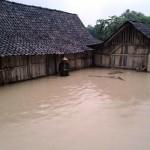 Loso, 65, warga Dukuh Sridarto RT 001, Desa Baleharjo, Sukodono, Sragen, menerjang air setinggi satu meter di depan rumah Wasinah, 75, yang bersebelahan dengan rumahnya saat banjir menggenangi dukuh setempat, Jumat (5/2/2016) petang. (Istimewa)