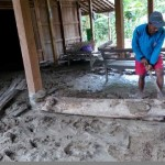 Ketua RT 012, Dusun Dukuh, Desa Jenar, Kecamatan Jenar, Sragen, membersihkan tumpukan lumpur akibat banjir bandang di rumah Sudar, 45, warga setempat, Senin (8/2/2016). (Moh. Khodiq Duhri/JIBI/Solopos)