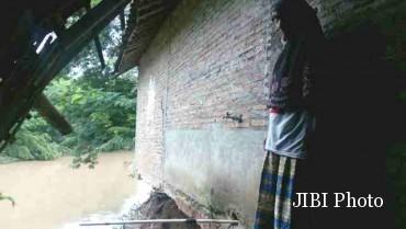 Suparmi, 50, mengamati fondasi bagian belakang rumahnya yang ambrol setelah diterjang arus Kali Grompol di Dusun Condong, RT 018, Masaran, Sragen, Jumat (12/2/2016). (Moh. Khodiq Duhri/JIBI/Solopos)