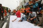 Sejumlah warga menandatangani kain saat juru parkir yang tergabung dalam Paguyuban Juru Parkir Malioboro (PJPM) menggelar aksi membagikan nasi bungkus dan menggalang dukungan di Jalan Malioboro, Yogyakarta, Jumat (11/03/2016). Dalam aksinya mereka meminta dukungan kepada pengguna jalan yang melintas dan menuntut kejelasan relokasi yang bernurani dan menolak relokasi kantong parkir ke Taman Parkir Portable di Taman Parkir Abu Bakar Ali. (JIBI/Harian Jogja/Desi Suryanto)