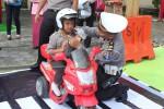 Anggota Polres Kulonprogo mengajarkan kepada seorang siswa TK mengenai cara memakai helm yang benar sebelum bermain di taman lalu lintas portabel yang diluncurkan di halaman Mapolres Kulonprogo, Sabtu (12/3/2016) kemarin. (Rima Sekarani I.N/JIBI/Harian Jogja)