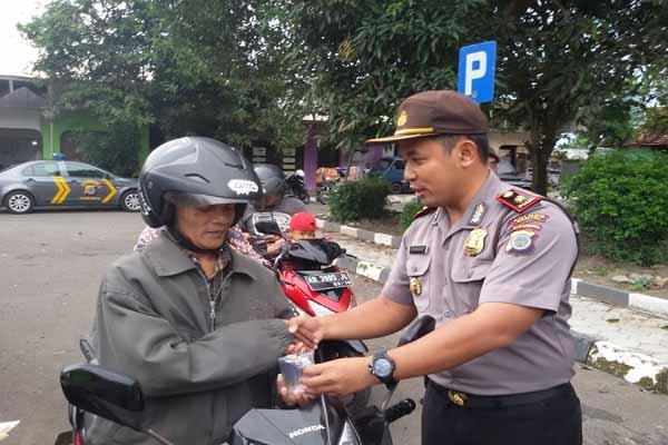 Polisi membagikan hadiah gelas bagi pengendara sepeda motor yang tertib lalu lintas pada razia yang digelar Polsek Bantul, Jumat (18/3/2016). (JIBI/Harian Jogja/Bhekti Suryani)