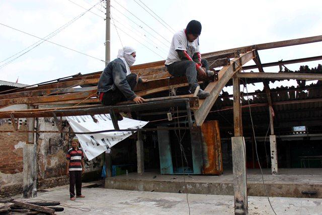 Dua pekerja memotong besi pada atap puing los di Pasar Karangpandan menggunakan gerinda, Senin (25/4/2016). (Sri Sumi Handayani/JIBI/Solopos)