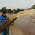 Seorang petugas menguras air banjir dengan mesin pompa yang membanjiri pemukiman tepi Sungai Ciliwung, Kampung Pulo, Jakarta Timur, Kamis (21/4/2016). Hujan deras yang mengguyur kawasan Jabodetabek sejak malam hingga pagi hari mengakibatkan banjir di beberapa pemukiman tepi sungai di Jakarta. (JIBI/Solopos/Antara/Regina Safri)