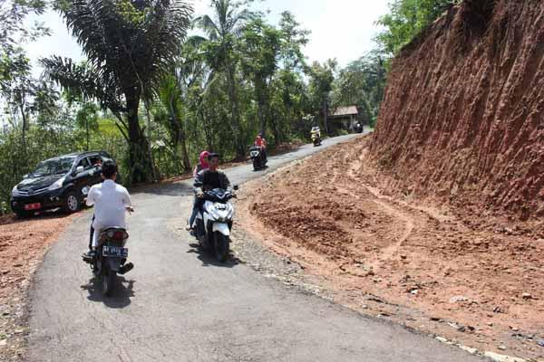 Beberapa warga melewati jalan yang sedang dilebarkan di wilayah Dusun Nglinggo, Desa Pagerharjo, Kecamatan Samigaluh, Kulonprogo, Selasa (19/4). Pelebaran jalan yang dilakukan dengan memapras tebing tersebut merupakan bagian dari program bedah menoreh.(Rima Sekarani I.N./JIBI/Harian Jogja)