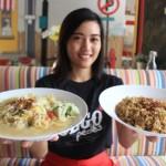 Salah satu karyawati Sego Pedes Restoran, Rosiani M, menunjukkan menu bakmie godok dan nasi goreng jowo yang ditawarkan di resto setempat, Kamis (21/4/2016). (Shoqib Angriawan/JIBI/solopos)
