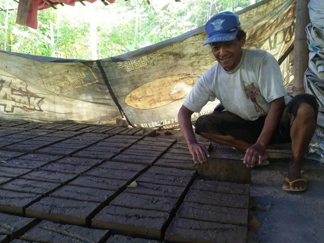 Pengrajin batu bata asal Jenangan, Ponorogo, Parlan, menata batu bata basah di rumah produksinya, Selasa (26/4/2016). (Abdul Jalil/JIBI/Madiunpos.com)