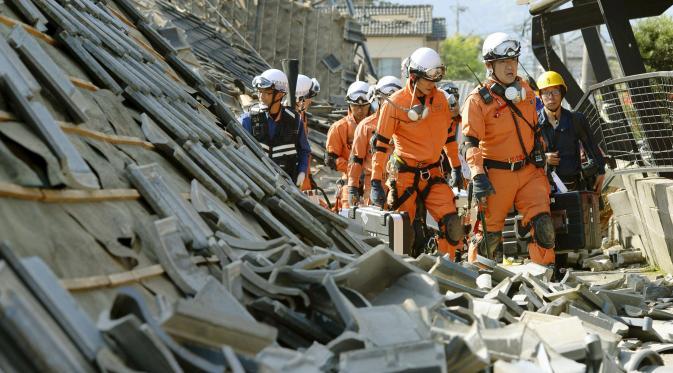 Petugas mencari korban di antara reruntuhan bangunan di Jepang (Reuters)