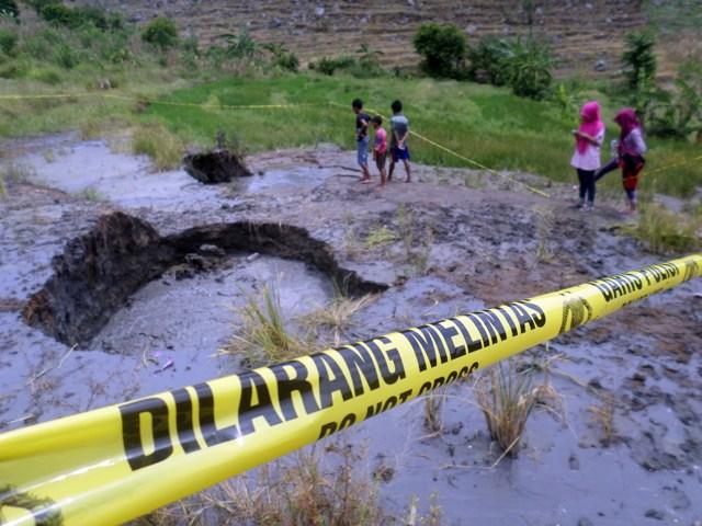 Pengunjung menerobos garis polisi yang dipasang di semburan air bercampur lumpur di Desa Jari, Gondang, Kabupaten Bojonegoro, Jawa Timur, Minggu (10/4/2016). (JIBI/Solopos/Antara/Aguk Sudarmojo)