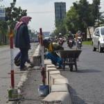 Sejumlah pekerja tengah memasang pembatas atau median jalan di Jalan Raya Solo-Sukoharjo mulai Simpang Empat Jln. Ciu hingga Simpang Empat Bulakrejo, Senin (18/4/2016)). (Bony Eko Wicaksono/JIBI/Solopos)