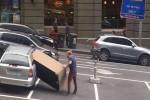 Seorang pria memasukan mebel berukuran besar ke dalam mobil kecil (Dailymail)