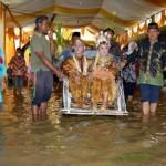 Sepasang mempelai di Desa Karangan, Kecamatan Balong, Ponorogo, Anggi Vicky Angelina dan Indra Kiki Harianto, naik becak saat resepsi pernikahan mereka dalam kondisi banjir, Selasa (12/4/2016). (Facebook-Melaz Pol)