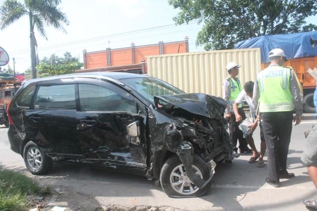 Polisi berusaha menderek mobil Toyota Avanza yang ringsek setelah terlibat kecelakaan karambol di kawasan Pungkruk, Sidoharjo, Sragen, Kamis (26/5/2016). (Istimewa)