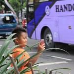Bocah pemburu klakson telolet berdiri di tepi jalan untuk mendapatkan gambar bus yang melintas, Rabu (18/5/2016). (Mariyana Ricky P.D./JIBI/JIBI/Solopos)